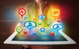 Meisje die een tablet met kleurrijke sociale pictogrammen en tekens voorstellen Stock Fotografie
