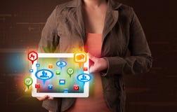 Meisje die een tablet met kleurrijke sociale pictogrammen en tekens voorstellen Stock Foto's