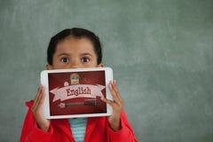 Meisje die een tablet met schoolpictogrammen houden op het scherm Stock Foto