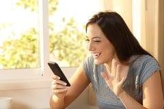 Meisje die in een telefoon videovraag golven Stock Foto's