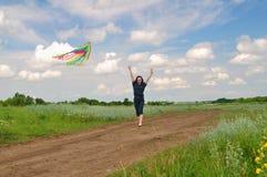 Meisje die een vlieger op een gebied vliegen Stock Afbeelding