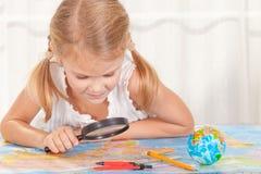 Meisje die een wereldkaart met een vergrootglas overwegen Stock Foto
