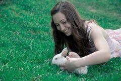 Meisje die een wit konijn houden stock foto