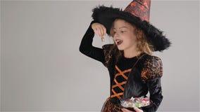 Meisje die een zwart-sinaasappelkleding en een grote hoed dragen Het meisje houdt snoepjes in handen De truc of behandelt, Hallow stock videobeelden