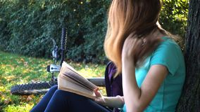 Meisje die en bij het park rusten lezen stock videobeelden