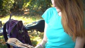 Meisje die en bij het park rusten lezen stock video