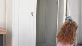 Meisje die en in de garderobe wordt doen schrikken verbergen die stock footage
