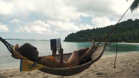 Meisje die en in de hangmat op een tropisch strand ontspannen lezen stock video