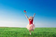 Meisje die en een stuk speelgoed bloem springen houden Royalty-vrije Stock Foto's