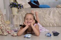 Meisje die en op de vloer glimlachen liggen Royalty-vrije Stock Foto's