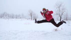 Meisje die en op de winterlandschap lopen springen, langzame motie stock footage