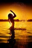Meisje die en op de zomerstrand zwemmen bespatten royalty-vrije stock afbeeldingen