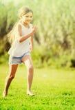 Meisje die en op gras lopen springen stock afbeelding