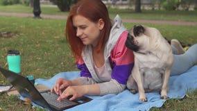 Meisje die en op laptop op een gazon met haar rond pug leggen typen stock footage