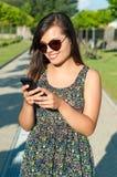 Meisje die en op telefoon zich buiten bevinden texting Stock Foto