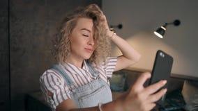 Meisje die foto met cellphone en glimlach in het huis nemen stock video
