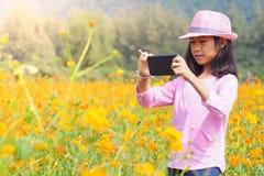 Meisje die foto mobiele telefoons op bloemengebied nemen royalty-vrije stock afbeelding