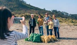 Meisje die foto nemen aan groep vrijwilligers na het schoonmaken van strand royalty-vrije stock afbeelding