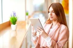 Meisje die freelancer een tablet in de koffie houden stock fotografie
