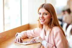 Meisje die freelancer een tablet in de koffie houden royalty-vrije stock fotografie