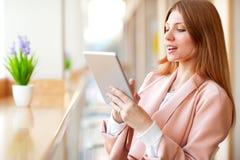 Meisje die freelancer een tablet in de koffie houden stock foto
