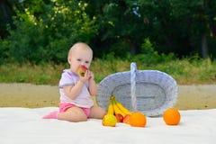 Meisje die fruit op het strand eten stock foto's
