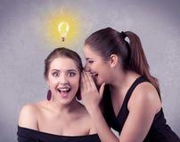 Meisje die geheime dingen vertellen aan haar meisje stock fotografie