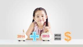 Meisje die geld op een spaarvarken met een nieuw jaar 2015 zetten Royalty-vrije Stock Afbeeldingen