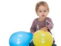 Meisje die gele en blauwe ballons houden Stock Foto's