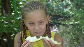 Meisje die gele meloen eten stock videobeelden