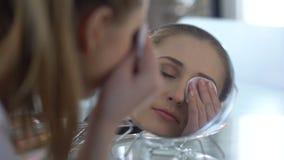 Meisje die gemakkelijk samenstelling uit ogen met nieuwe lotion, het testen verwijderen van vlekkenmiddelen stock video