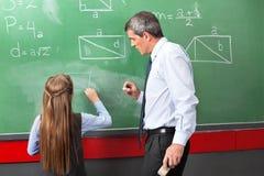 Meisje die Geometrische Vormen aan boord trekken met Stock Foto