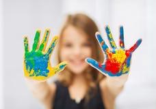 Meisje die geschilderde handen tonen stock afbeelding