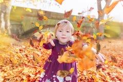 Meisje die gevallen bladeren werpen Royalty-vrije Stock Foto's