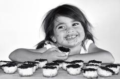 Meisje die gevangen etend chocoladekoekjes worden Stock Foto's