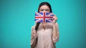Meisje die gezicht behandelen met Britse vlag, lerend taal, onderwijs en reis stock video