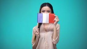 Meisje die gezicht behandelen met Franse vlag, lerend taal, onderwijs en reis stock footage