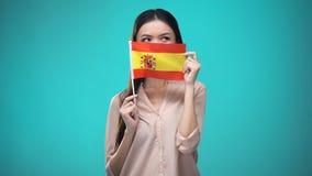 Meisje die gezicht behandelen met Spaanse vlag, lerend taal, onderwijs en reis stock footage