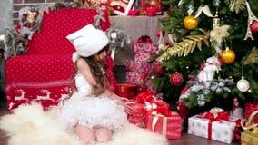 Meisje die giften, het kostuum van kindcarnaval dichtbij de Kerstboom, de wintervakantie van Nieuwjaar, de medewerker van kijken stock videobeelden