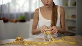 Meisje die glas water met band meten, verhongerend lichaam, uitputting, anorexie stock afbeeldingen