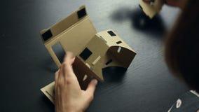 Meisje die glazen van een de Virtuele Werkelijkheidskarton assembleren stock footage
