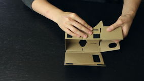 Meisje die glazen van een de Virtuele Werkelijkheidskarton assembleren stock video