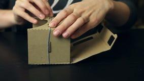 Meisje die glazen van een de Virtuele Werkelijkheidskarton assembleren stock videobeelden