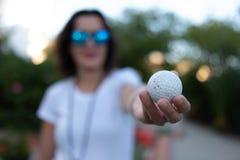 Meisje die golfbal in haar handen tonen stock afbeelding