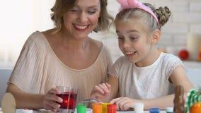 Meisje die in grappige hoofdband ei zetten in rode voedselkleuring, Pasen-tradities stock video
