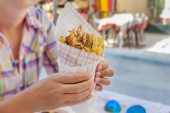 Meisje die Griekse gyroscoop met gebraden gerechten dicht omhoog op lijst houden Stock Afbeelding