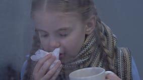 Meisje die griep aan symptomen lijden, hete thee drinken en, epidemieën niezen stock video