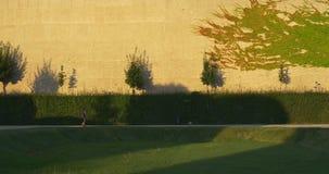 Meisje die in groen park dichtbij muur met klimop lopen stock footage