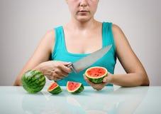 Meisje die groot mes voor het snijden van sappige rode kleine watermeloenen gebruiken stock fotografie