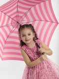 Meisje die grote, gestreepte paraplu houden stock foto